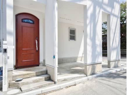 白い外観に木目のドアがお洒落なアクセントとなっています