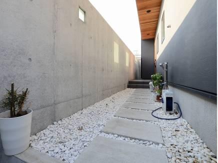 人目が気にならないコンクリート造の玄関までのアプローチ。